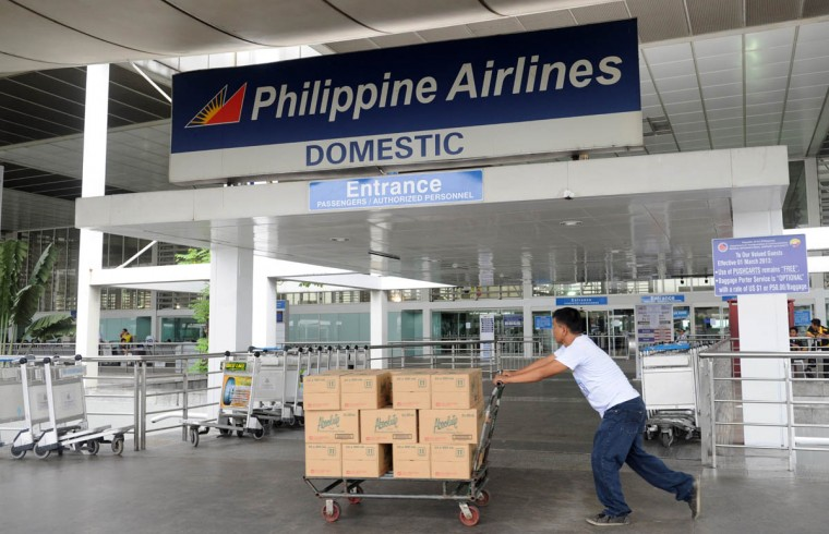 A delivery man passes a Philippine Airlines sign at the domestic flights entrance of Manila's International airport on November 8, 2013. One of the most intense typhoons ever recorded tore into the Philippines on November 8, triggering flash floods and ripping down buildings as millions of people huddled indoors. (Jay Directo/Getty Images)