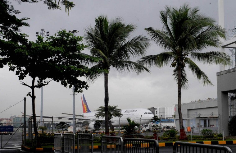 A Philippine Airlines plane stands parked on the tarmac at Manila's International airport on November 8, 2013. One of the most intense typhoons ever recorded tore into the Philippines on November 8, triggering flash floods and ripping down buildings as millions of people huddled indoors. (Jay Directo/Getty Images)