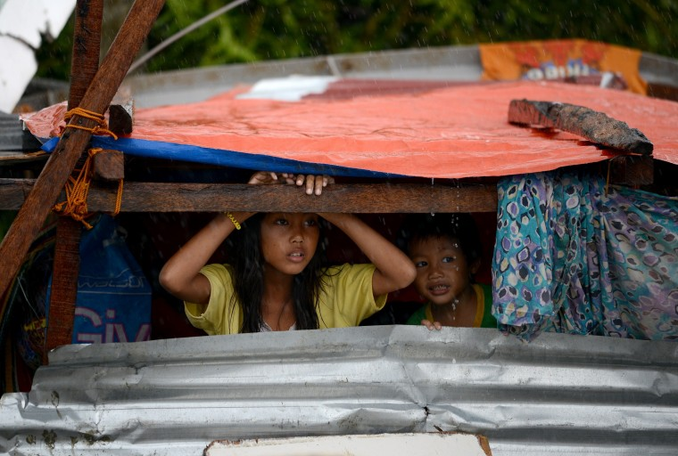 Children peek out from their makeshift shelter in Tacloban, on the eastern island of Leyte on November 10, 2013. A super typhoon that destroyed entire towns across the Philippines is believed to have killed more than 10,000 people, authorities said on November 10, which would make it the country's deadliest recorded natural disaster. (Noel Celis/AFP/Getty Images)