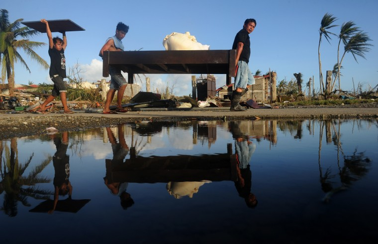 Residents carry furniture taken from a hotel in Palo, eastern island of Leyte on November 10, 2013, three days after devastating Super Typhoon Haiyan hit the area on November 8. The death toll from a super typhoon that decimated entire towns in the Philippines could soar well over 10,000, authorities warned on November 10, making it the country's worst recorded natural disaster. (Noel Celis/AFP/Getty Images)