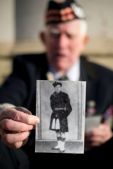 John Mills, a veteran of World War II and 27 years in the armed forces, poses with a portrait of himself taken in Japan in1946, after taking part in the Remembrance Sunday service in central London on November 10, 2013. (Leon Neal/Getty Images)