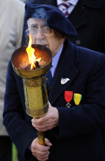 A veteran holds the flame of the remembrance as he takes part in a ceremony in tribute to seven unknown soldiers, on November 10, 2013 at the Faubourg-Pave French Cemetery in Verdun, eastern France. Eight bodies of soldiers who served in the French uniform, but that could not be identified were exhumed in eight areas where had occurred the bloodiest battles: in Flanders, Artois, in the Somme, in Ile-de-France, at the Chemin des Dames, in Champagne, Lorraine and Verdun. One of the coffin was moved in 1920 under the Arc de Triomphe, in Paris, but the other seven remained in Verdun. (Jean-Christophe Verhaegen/Getty Images)