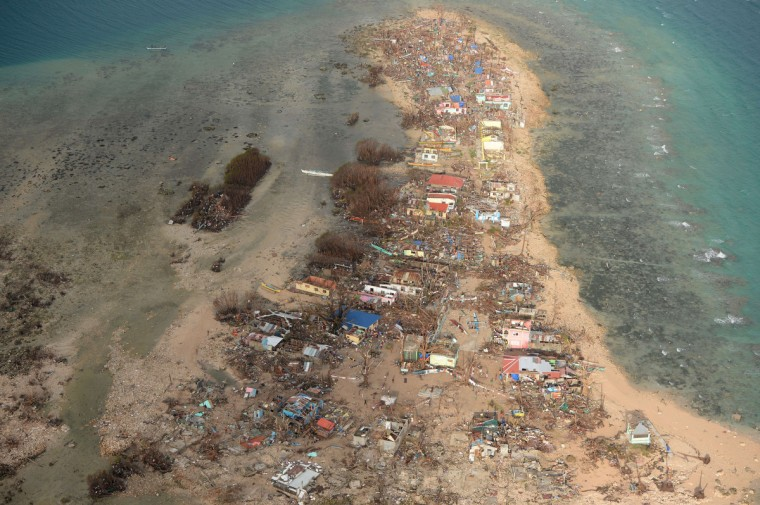 This aerial shot shows destroyed houses on Victory Island off of the town of Guiuan in Eastern Samar province, central Philippines on November 11, 2013, four days after devastating Typhoon Haiyan hit the country. Philippines rescue workers struggled to bring aid to famished and destitute survivors on November 11 after the super typhoon that may have killed more than 10,000 people, in what is feared to be the country's worst natural disaster. (Ted Aljibe/Getty Images)