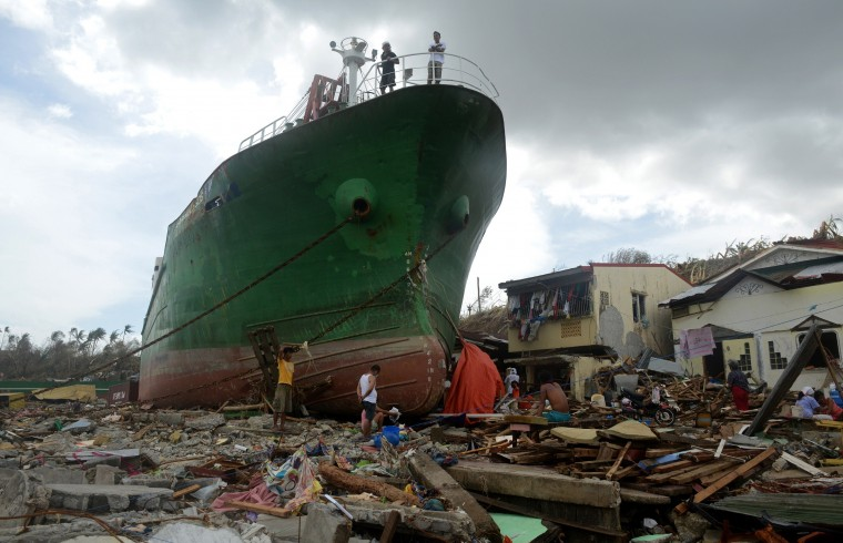 People walk amongst debris next to a ship washed ashore in the aftermath of Super Typhoon Haiyan at Anibong in Tacloban, eastern island of Leyte on November 11, 2013. Hundreds of Philippine soldiers and police poured into a city devastated by Super Typhoon Haiyan on November 11 to try to contain looting that threatens an emergency relief effort. (Noel Celis/AFP/Getty Images)