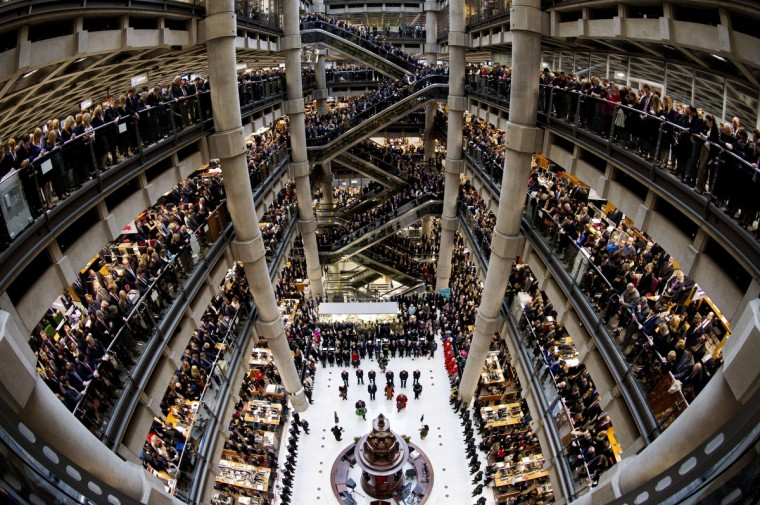 Brokers and underwriters line the balconies and escalators of the Lloyd's of London building in central London, on November 11, 2013, during a two-minute silence observed in memory of Britain's war dead. The service at Lloyd's of London is observed with the ringing of the Lutine Bell and the laying of wreaths before the Book of Remembrance in addition to the two-minute silence. (Adrian Dennis/Getty Images)