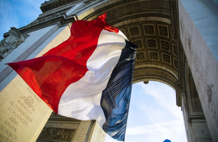 Morning sunlight shines on a giant French flag on November 11, 2013 ahead of a ceremony commemorating the end of World War I at the Arch of Triumph in Paris. (Ian Langsdon/Getty Images)