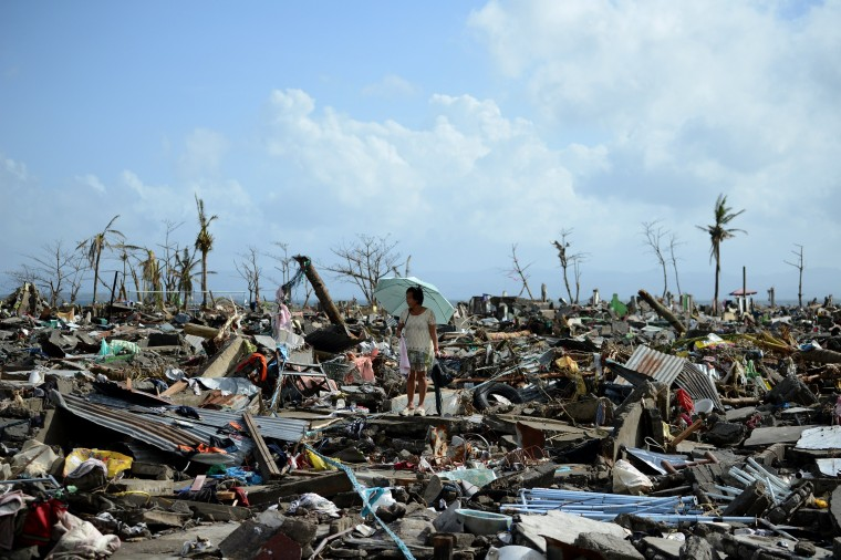 A surivor walks among the debris of houses destroyed by Super Typhoon Haiyan in Tacloban in the eastern Philippine island of Leyte on November 11, 2013. The United States, Australia and the United Nations mobilised emergency aid to the Philippines as the scale of the devastation unleashed by Super Typhoon Haiyan emerged on November 11. (Noel Celis/AFP/Getty Images)