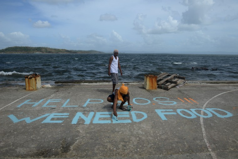 """A man paints a message on a baskeball court that reads """"Help SOS We Need Food"""" at Anibong in Tacloban, eastern island of Leyte on November 11, 2013. Hundreds of Philippine soldiers and police poured into a city devastated by Super Typhoon Haiyan on November 11 to try to contain looting that threatens an emergency relief effort. Children peek out from their makeshift shelter in Tacloban, on the eastern island of Leyte on November 10, 2013. A super typhoon that destroyed entire towns across the Philippines is believed to have killed more than 10,000 people, authorities said on November 10, which would make it the country's deadliest recorded natural disaster. (Noel Celis/AFP/Getty Images)"""