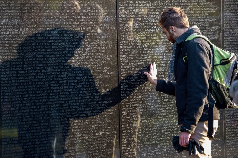 An unidentified man is seen touching the Viet Nam Memorial wall on Veteran's Day November 11, 2013 as he pays his respects to fallen veterans in Washington, DC. (Paul J. Richards/Getty Images)