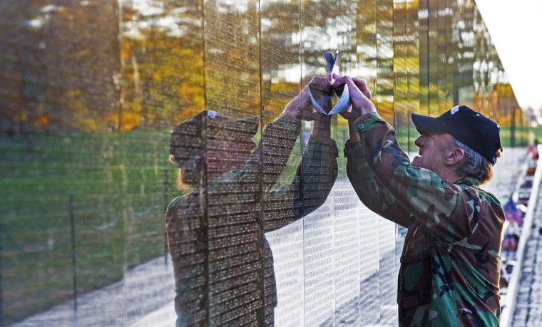 An unidentified Viet Nam veteran traces a name off a fallen soldier off the Viet Nam Memorial wall seen here on Veteran's Day November 11, 2013 as he pays his respects in Washington, DC. (Paul J. Richards/Getty Images)