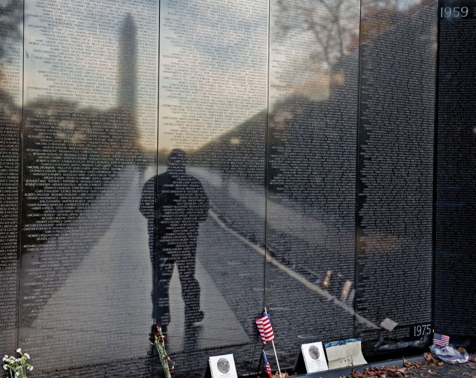 An unidentified man is seen in the reflection of the Viet Nam Memorial wall on Veteran's Day November 11, 2013 as he pays his respects to fallen veterans in Washington, DC. (Paul J. Richards/Getty Images)