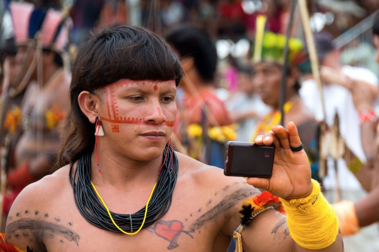 An indigenous man records participants of the bow and arrow competition with his mobile phone during the XII International Games of Indigenous Peoples in Cuiaba, Mato Grosso state, Brazil on November 12, 2013. 1500 natives from 49 Brazilian ethnic groups and from another 17 countries are gathering in Cuiaba until November 16 to compete in some 30 athletic disciplines, many of their own. (Christophe Simon/Getty Images)