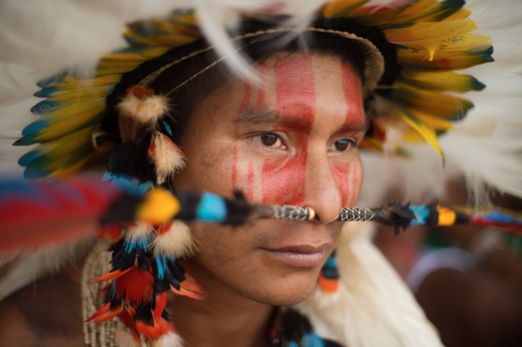 A Brazilian indigenous man of the Rikbaktsa tribe watches the bow and arrow competition during the XII International Games of Indigenous Peoples in Cuiaba, Mato Grosso state, Brazil. 1500 natives from 49 Brazilian ethnic groups and from another 17 countries are gathering in Cuiaba until November 16 to compete in some 30 athletic disciplines, many of their own. (Christophe Simon/Getty Images)