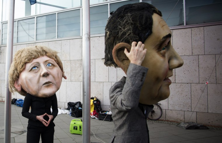 Activists wear masks featuring German Chancellor Angela Merkel (L) and the leader of the social democratic SPD party Sigmar Gabriel as they demonstrate for the introduction of nationwide referendums in front of the venue where members of the social democratic SPD party and members of the conservative CDU/CSU union met for coalition talks on November 13, 2013 in Berlin. (Johannes Eisele/Getty Images)