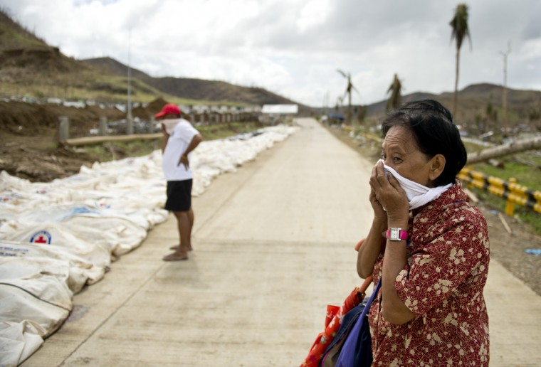 "A woman covers her nose and mouth as she stopped to look at the body bags containing the remains of some 170 dead collected from the rubble at the ""Cemetery of the hills"", one of three mass burial sites where they so far have received one thousand typhoon victims in Tacloban. Philippine President Benigno Aquino blamed the slow response to the ravages of Typhoon Haiyan on the total collapse of local government in the face of the storm's unprecedented destructive power. (Odd Andersen/Getty Images)"