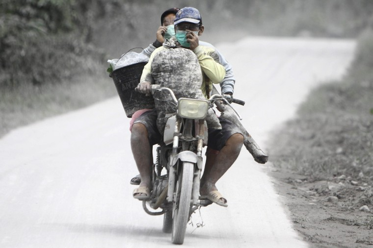 Farmers ride their motorcycle along a road one day after Mount Sinabung erupted in Karo, northern Sumatra island. Two volcanoes erupted in Indonesia on November 18, with one forcing flights to be rerouted and stopping thousands of people who had already been evacuated from returning home. (Kharisma Tarigan/Getty Images)