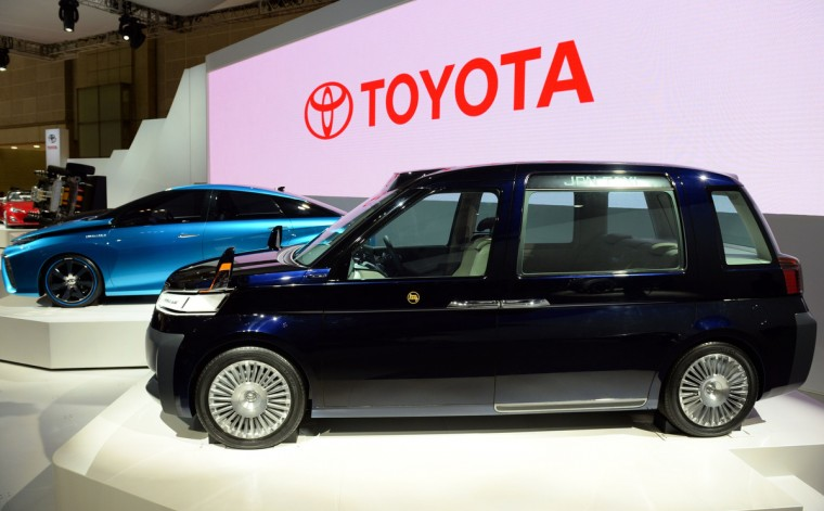"Toyota Motor Corp.'s ""JPN Taxi"" (R) is displayed beside the ""FCV concept"" vehicle (L) at the company's booth at the Tokyo Motor Show 2013 in Tokyo on November 20, 2013. (Toshifumi Kitamura/Getty Images)"