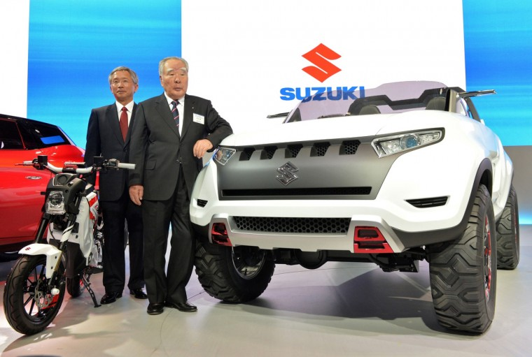 """Japan's automaker Suzuki Motor president Osamu Suzuki (R) and vice president of Osamu Honda pose next to the company's concept vehicle """"X-Lander"""" and electric motorcycle """"Extrigger"""" at a press preview of the Tokyo Motor Show in Tokyo on November 20, 2013. (Yoshikazu Tsuno/Getty Images)"""