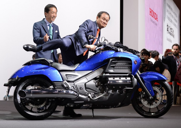 Honda Motor President Takanobu Ito (C) straddles a 1,800cc motorcycle Goldwing F6C beside senior managing officer Sho Minekawa (L) during a press briefing at the company's booth at the Tokyo Motor Show 2013 in Tokyo on November 20, 2013. The biennial motor show, held from November 20 to December 1, features domestic makers of passenger cars, commercial vehicles and trucks alongside most of their European competitors. (Toru Yamanaka/Getty Images)