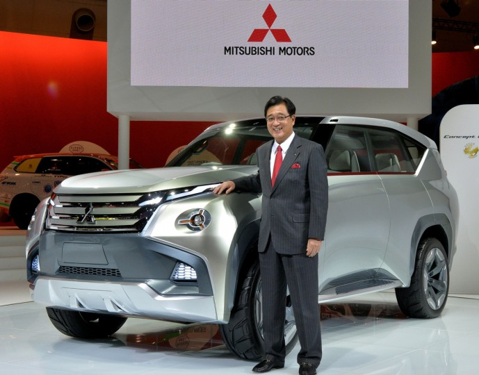"""Japan's automaker Mitsubishi Motors president Osamu Masuko displays the new concept plug-in hybrid vehicle (PHEV) """"Concept GC-PHEV"""" at the press preview of the Tokyo Motor Show in Tokyo on November 20, 2013. (Yoshikazu Tsuno/Getty Images)"""