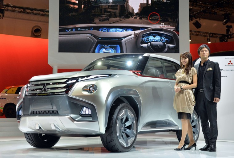 "Models display Japanese automaker Mitsubishi Motors' concept plug-in hybrid vehicle (PHEV) ""Concept GC-PHEV"" at the press preview of the Tokyo Motor Show in Tokyo on November 20, 2013. (Yoshikazu Tsuno/Getty Images)"