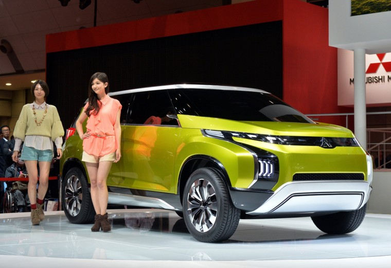 """Models display Japanese automaker Mitsubishi Motors' concept minivan """"Concept AR"""", equipped with a 1.1-litre turbo charged engine for a six-seater body at the press preview of the Tokyo Motor Show in Tokyo on November 20, 2013. (Yoshikazu Tsuno/Getty Images)"""