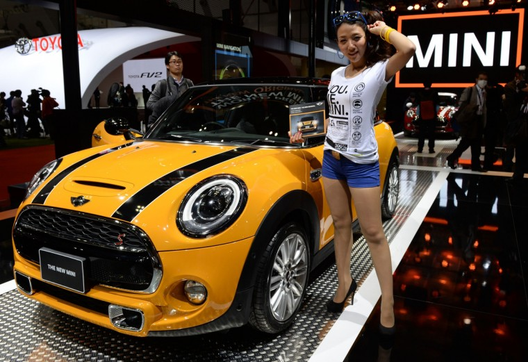 """A model stands beside the newly designed """"New Mini Cooper S"""" at the Tokyo Motor Show in Tokyo on November 20, 2013. (Toshifumi Kitamura/Getty Images)"""