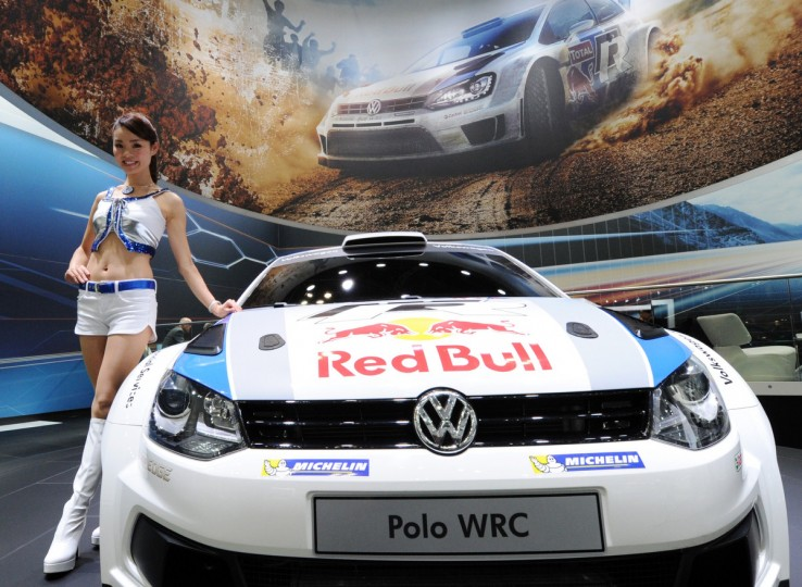 "A model stands beside the Volkswagen's world rally car ""Polo WRC"" at the Tokyo Motor Show in Tokyo on November 20, 2013. (Toshifumi Kitamura/Getty Images)"