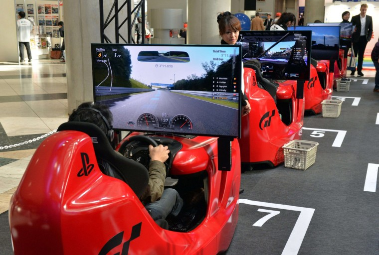 """People enjoy driving the videogame """"Gran-Turismo 6"""" of Sony Computer Entertainment as which will be launched next month at the press preview of the Tokyo Motor Show in Tokyo on November 20, 2013. (Yoshikazu Tsuno/Getty Images)"""