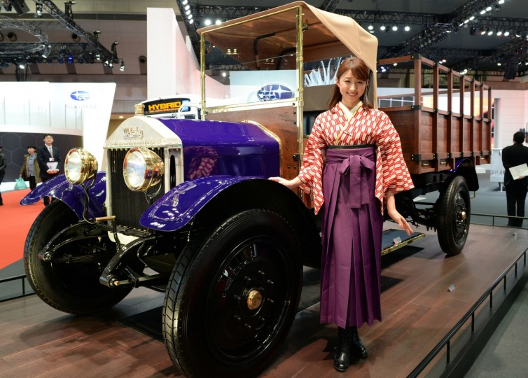 A model stands beside a 1924 Wolseley CP 1.5-ton truck at the Isuzu booth during the Tokyo Motor Show in Tokyo on November 20, 2013. The motor show, held from November 20 to December 1, features domestic makers of passenger cars, commercial vehicles and trucks alongside most of their European competitors. (Toshifumi Kitamura/Getty Images)