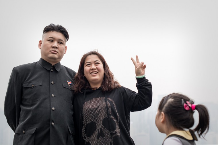 A Hong Kong born Australian named Howard (L) poses with a tourist in Hong Kong. Howard is considered the world's first professional Kim Jong-Un impersonator. (Philippe Lopez/Getty Images)