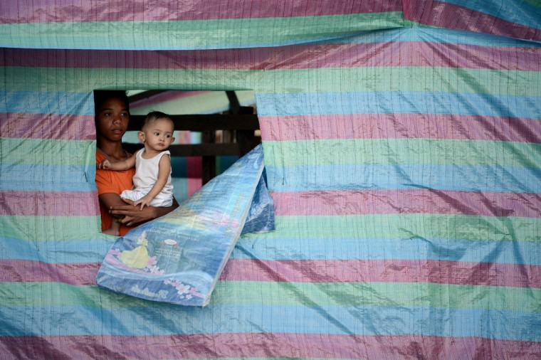 A boy holds his baby brother at a makeshift house at the bay of Tacloban, Leyte province. The swift US humanitarian response to the devastation of Super Typhoon Haiyan highlights the need to expand America's military presence in the Philippines, Foreign Secretary Albert del Rosario said on November 25. (Noel Celis/Getty Images)