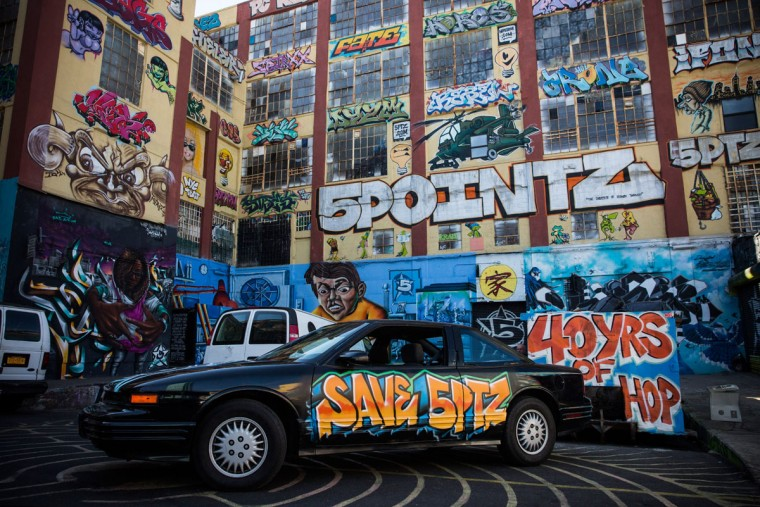 "A graffiti painted car is parked in front of the 5 Pointz Building, a landmark in the New York graffiti scene that has attracted artists from around the globe, on October 28, 2013 in the Long Island City neighborhood of the Queens borough of New York City. The artists that have been using 5 Pointz to paint for the past two decades are currently in a battle with the building's owners, who want to tear the building down to build apartment high rises worth $400 million. The 5 Pointz artistic community have also called on street artist Banksy who is currently in the midst of a high profile ""month in residence"" series, creating work through out the streets of New York, to weigh in on the battle, though so far the artist has stayed silent. Meres One says he is prepared to chain himself to the building, should demolition move forward. (Andrew Burton/Getty Images)"