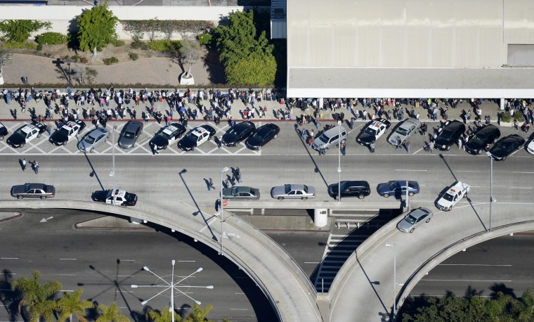 Passangers stand on the sidewalk after being evacuated from Terminal 3 and Terminal 2 after a shooting at Los Angeles International Airport November 1, 2013 in Los Angeles, California. (Kevork Djansezian/Getty Images)
