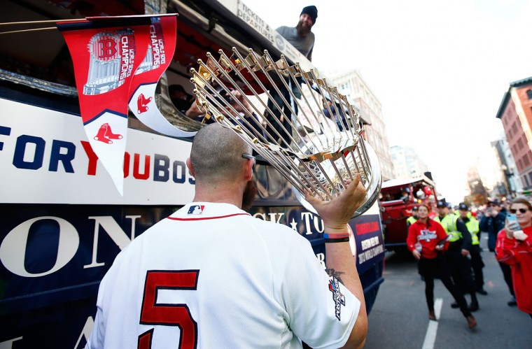 Jonny Gomes #5 of the Boston Red Sox carries the World Series trophy near the finish line of the Boston Marathon on Boylston Street during the World Series victory parade on November 2, 2013 in Boston, Massachusetts. (Jared Wickerham/Getty Images)