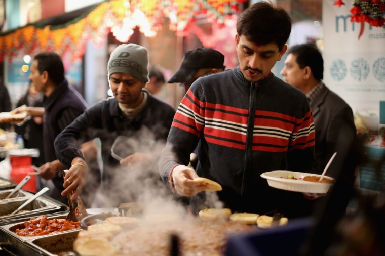 Chefs cook traditional food on the strets to celebrate the Hindu festival of Diwali on November 3, 2013 in Leicester, United Kingdom. Up to 35,000 people attended the Diwali festival of light in Leicester's Golden Mile in the heart of the city's Asian community. The festival is an opportunity for Hindus to honour Lakshmi, the goddess of wealth and other gods. Leicester's celebrations are one of the biggest in the world outside India. (Christopher Furlong/Getty Images)