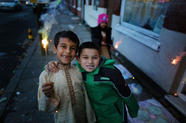 Young children hold sparklers as the home of the Barut family is decorated to celebrate the Hindu festival of Diwali on November 3, 2013 in Leicester, United Kingdom. Up to 35,000 people attended the Diwali festival of light in Leicester's Golden Mile in the heart of the city's Asian community. The festival is an opportunity for Hindus to honour Lakshmi, the goddess of wealth and other gods. Leicester's celebrations are one of the biggest in the world outside India. (Christopher Furlong/Getty Images)