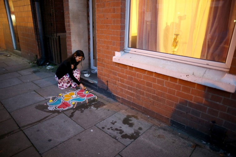 A woman decorates the pavement outside her home with sand, known as rangoli art, to celebrate the Hindu festival of Diwali on November 3, 2013 in Leicester, United Kingdom. Up to 35,000 people attended the Diwali festival of light in Leicester's Golden Mile in the heart of the city's Asian community. The festival is an opportunity for Hindus to honour Lakshmi, the goddess of wealth and other gods. Leicester's celebrations are one of the biggest in the world outside India. (Christopher Furlong/Getty Images)