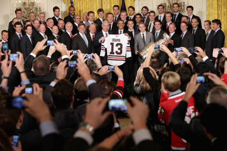 Guests use mobile phone cameras to record U.S. President Barack Obama as he poses for photographs with the National Hockey League 2013 champion Chicago Blackhawks in the East Room of the White House November 4, 2013 in Washington, DC. This is the second visit to the White House in as many years for the Blackhawks, who won the Stanley Cup in 2010. (Chip Somodevilla/Getty Images)