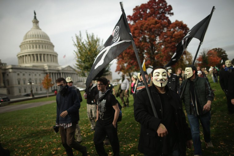 "People march to the U.S. Captiol during the ""Million Mask March"" November 5, 2013 in Washington, DC. Organized by members of Anonymous, WikiLeaks, The Pirate Party, Occupy Wall Street and other hacktivist movements, demonstrators marched on political landmarks and institutions around the world on Guy Fawkes Day. (Chip Somodevilla/Getty Images)"