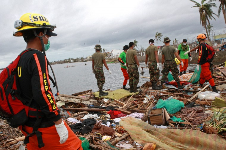 Military personnel and members of the Philippine's Special Reaction Unit search for the bodies of victims of Typhoon Haiyan on November 12, 2013 near Tacloban, Leyte, Philippines. Typhoon Haiyan, packing maximum sustained winds of 195 mph (315 kph), slammed into the southern Philippines and left a trail of destruction in multiple provinces, forcing hundreds of thousands to evacuate and making travel by air and land to hard-hit provinces difficult. Around 10,000 people are feared dead in the strongest typhoon to hit the Philippines this year. (Jeoffrey Maitem/Getty Images)