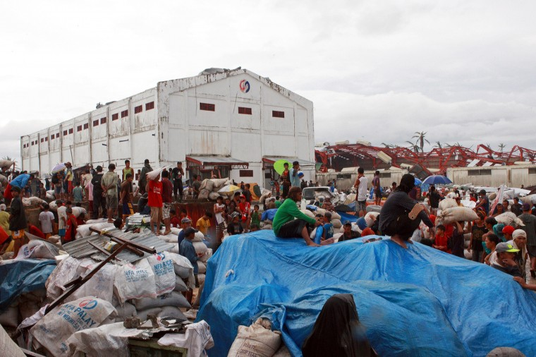 Residents search for food at a damaged warehouse belonging to the National Food Authority in the aftermath of Typhoon Haiyan on November 12, 2013 in Alangalang, Leyte, Philippines. Typhoon Haiyan, packing maximum sustained winds of 195 mph (315 kph), slammed into the southern Philippines and left a trail of destruction in multiple provinces, forcing hundreds of thousands to evacuate and making travel by air and land to hard-hit provinces difficult. Around 10,000 people are feared dead in the strongest typhoon to hit the Philippines this year. (Jeoffrey Maitem/Getty Images)