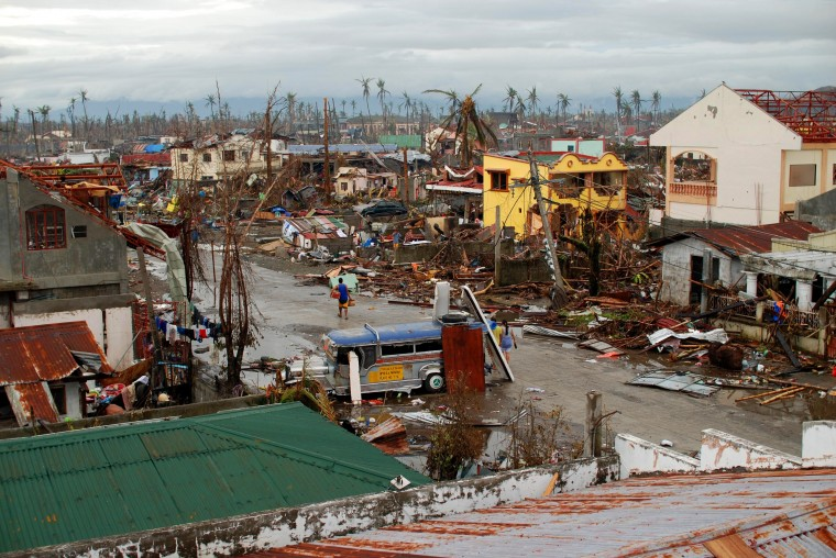 A man carrying provisions walks through an area devastated by Typhoon Haiyan on November 12, 2013 in Leyte, Philippines. Four days after the typhoon devastated the region many have nothing left, they are without food or power and most lost their homes. Around 10,000 people are feared dead in the strongest typhoon to hit the Philippines this year. (Dondi Tawatao/Getty Images)