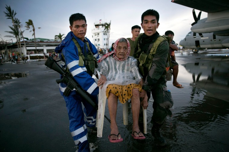 An elderly lady is carried to a waiting C130 aircraft during the evacuation of hundreds of survivors of Typhoon Haiyan on November 12, 2013 in Tacloban, Philippines. Four days after the typhoon devastated the region many have nothing left, they are without food or power and most lost their homes. Around 10,000 people are feared dead in the strongest typhoon to hit the Philippines this year. (Paula Bronstein/Getty Images)