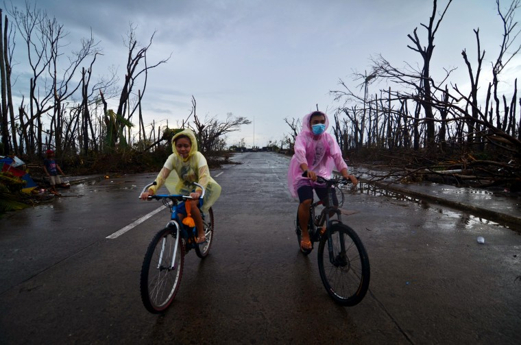 Two people ride bikes through an area devastated by Typhoon Haiyan on November 12, 2013 in Leyte, Philippines. Four days after the typhoon devastated the region many have nothing left, they are without food or power and most lost their homes. Around 10,000 people are feared dead in the strongest typhoon to hit the Philippines this year. (Dondi Tawatao/Getty Images)