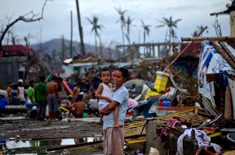A woman holds a child surrounded by debris in an area devastated by Typhoon Haiyan on November 12, 2013 in Leyte, Philippines. Four days after the Typhoon Haiyan devastated the region many have nothing left, they are without food or power and most lost their homes. Around 10,000 people are feared dead in the strongest typhoon to hit the Philippines this year. (Dondi Tawatao/Getty Images)