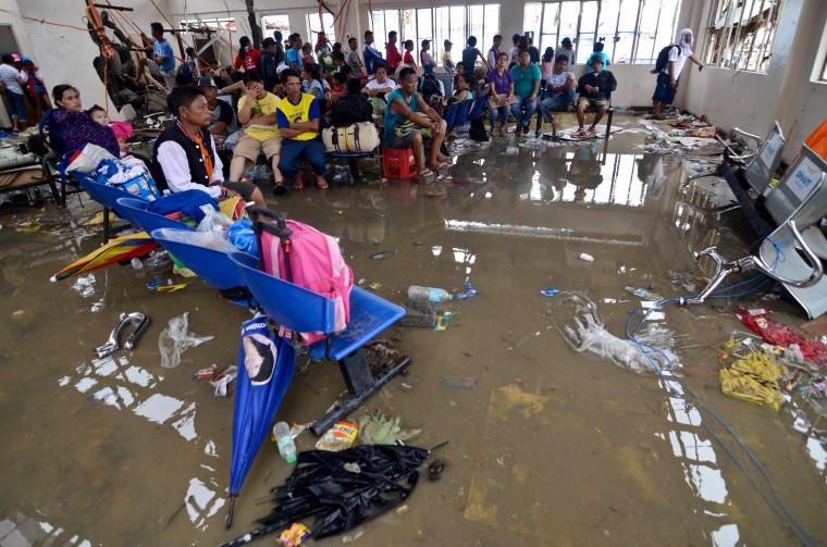 Evacuees wait for their flight inside an airport lounge flooded with water in the aftermath of Typhoon Haiyan on November 12, 2013 in Leyte, Philippines. Four days after the Typhoon Haiyan devastated the region many have nothing left, they are without food or power and most lost their homes. Around 10,000 people are feared dead in the strongest typhoon to hit the Philippines this year. (Photo by Dondi Tawatao/Getty Images)