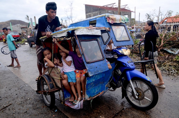 Children pack a motorbike's sidecar as they travel along a street in an area devastated by Typhoon Haiyan on November 12, 2013 in Leyte, Philippines. Four days after the Typhoon Haiyan devastated the region many have nothing left, they are without food or power and most lost their homes. Around 10,000 people are feared dead in the strongest typhoon to hit the Philippines this year. (Dondi Tawatao/Getty Images)