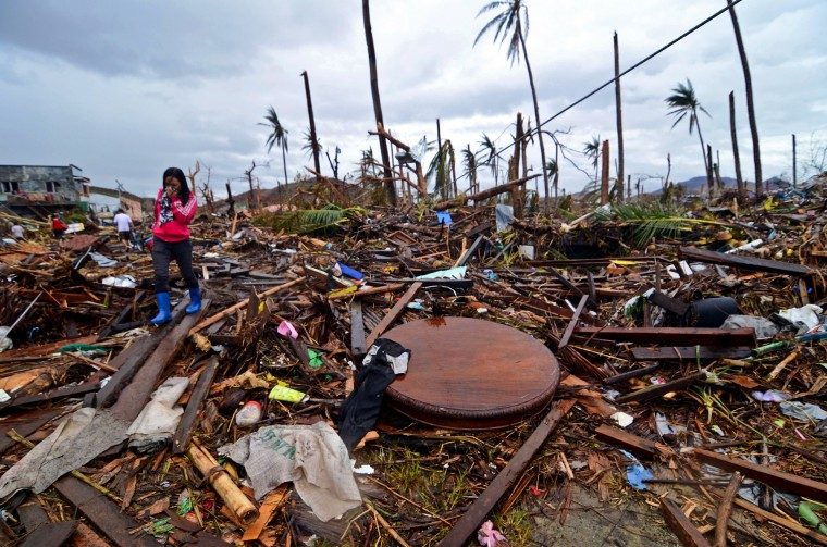 A woman walks through a road filled with debris in an area devastated by Typhoon Haiyan on November 12, 2013 in Leyte, Philippines. Four days after the Typhoon Haiyan devastated the region many have nothing left, they are without food or power and most lost their homes. Around 10,000 people are feared dead in the strongest typhoon to hit the Philippines this year. (Dondi Tawatao/Getty Images)