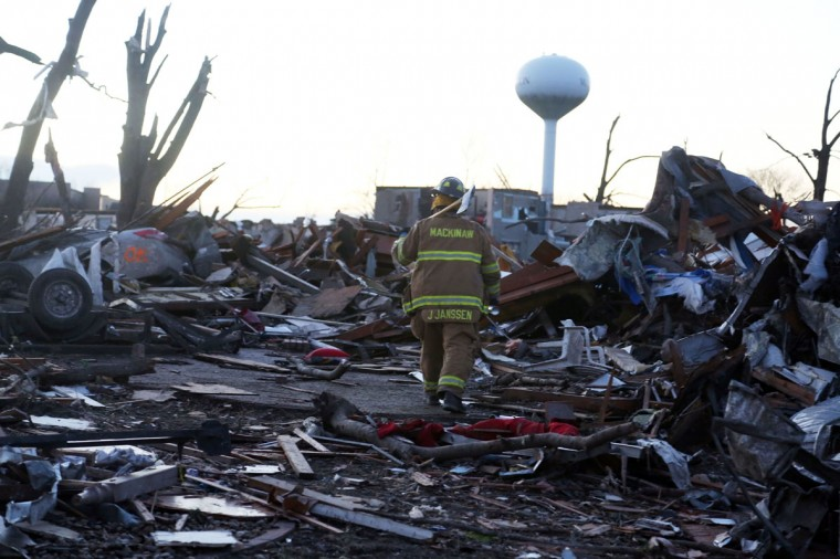 Jeremy Janssen of Mackinaw Fire Department walks through debris along Elgin Avenue after a tornado struck Washington, Ill. Several tornadoes touched down across the Midwest, with at least three people reported dead in Illinois. (Photo by Tasos Katopodis/Getty Images)
